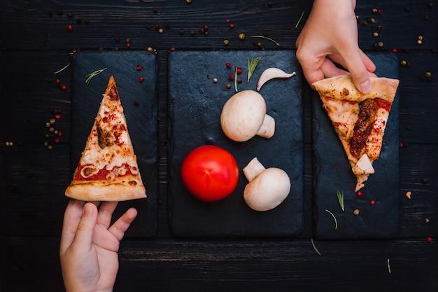 Babyhände und frische pizza auf einem schwarzen holztisch