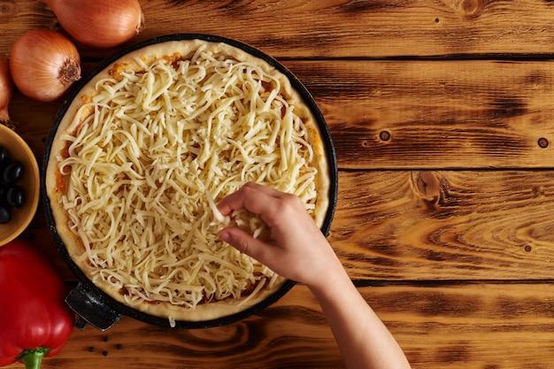 Babyhand legt käse auf rohe pizza auf holztisch mit kopienraum. draufsicht. rustikal.