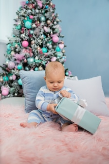 Babyjunge in einem gestreiften overall sitzt und öffnet ein geschenk auf dem hintergrund eines weihnachtsbaumes. vertikale ausrichtung