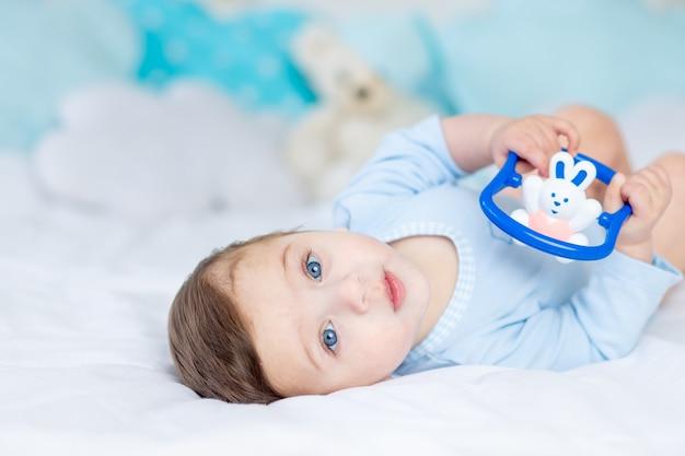 Babyjunge mit einem nagetier zum zahnen oder einer rassel auf dem bett zum schlafen, gesundes glückliches kleines baby in einem blauen bodysuit, der spielt