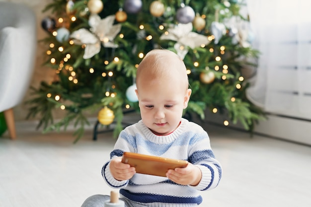 Babykinderporträt mit dem weihnachtsbaum. weihnachtsnettes kleinkind. familienurlaub konzept. kinderspielzimmer. weihnachten im kinderzimmer. kind mit smartphone.