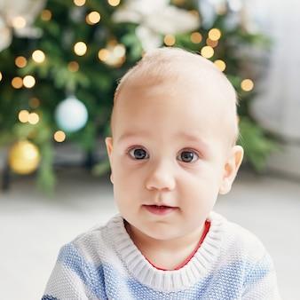 Babykinderporträt mit dem weihnachtsbaum. weihnachtsnettes kleinkind. familienurlaub konzept. kinderspielzimmer. weihnachten im kinderzimmer.