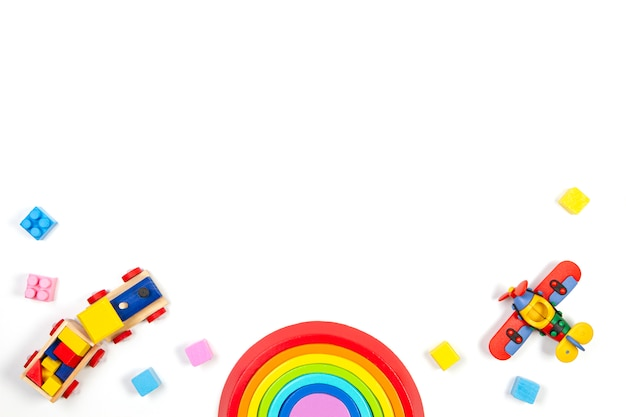 Babykinderspielzeughintergrund mit hölzernem zug, regenbogen, flugzeug und bunten blöcken