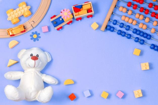 Babykinderspielzeugrahmen auf blauem hintergrund. draufsicht. flach liegen. kopieren sie platz für text