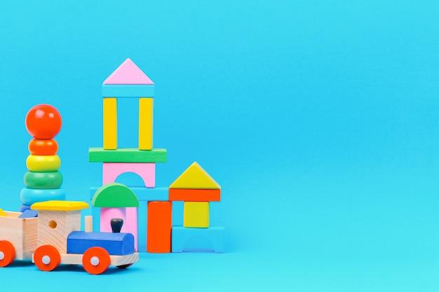 Babykindspielzeughintergrund mit buntem holzspielzeug auf hellblauem hintergrund.