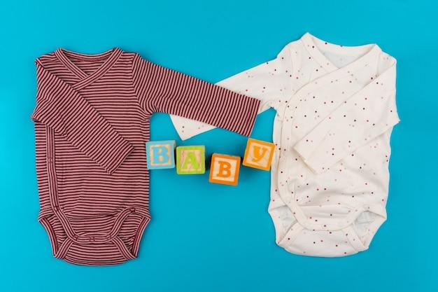 Babykleidung auf blauem hintergrund draufsicht