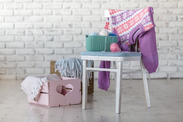 Babykleidung auf stuhl im weißen raum