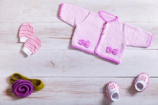 Babykleidung auf weißem hölzernem hintergrund, flache lage