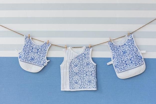 Babykleidung, die am seil auf grau hängt