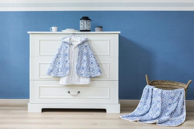 Babykleidung, die am seil auf grauem hintergrund hängt