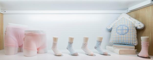 Babykleidung, die an der wäscheleine, auf hellem hintergrund hängt