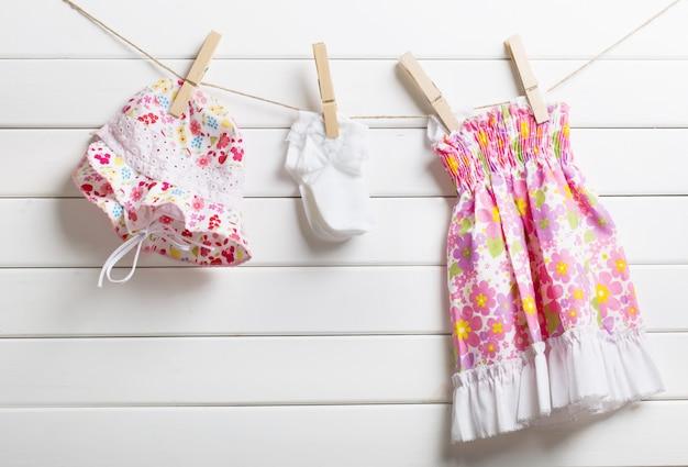 Babykleidung, die an wäscheleine, auf hölzernem hintergrund hängt
