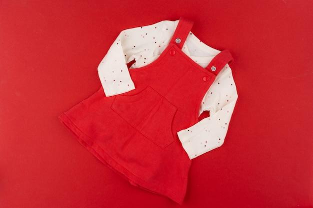 Babykleidung draufsicht auf rotem hintergrund