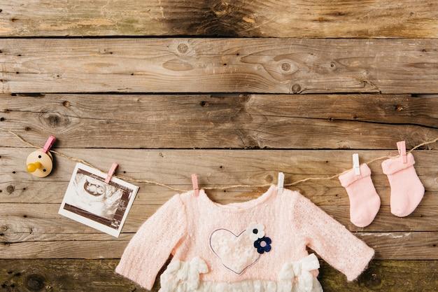 Babykleidung; socken; schnuller- und sonographiebild, das an der wäscheleine mit wäscheklammern gegen hölzerne wand hängt