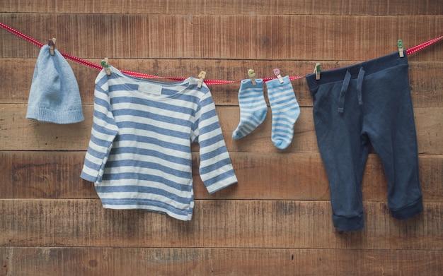 Babykleidung trocknete an der wäscheleine und am hölzernen hintergrund