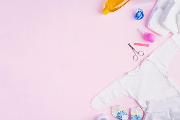 Babykleidung und andere sachen für kind auf rosa hintergrund. neugeborenen-baby-konzept. draufsicht