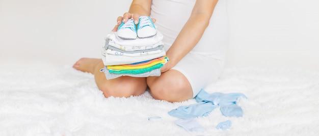 Babykleidung und eine schwangere frau.