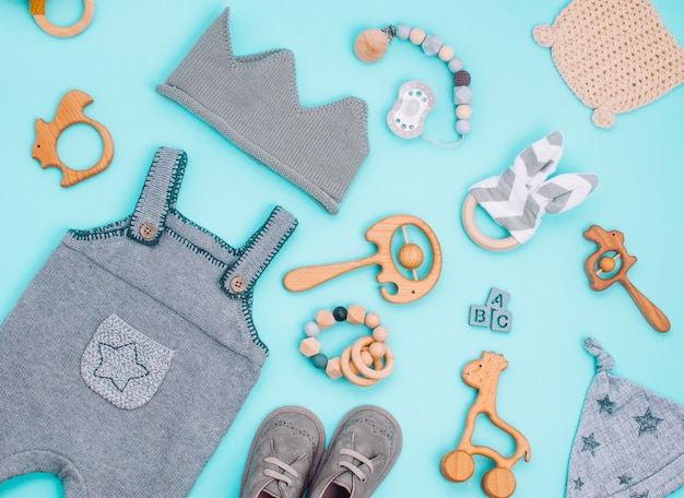 Babykleidung und holzspielzeug auf hellblau