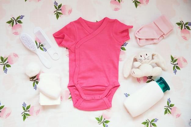 Babykleidung und notwendigkeiten auf hellem stoffhintergrund sanfte weiche und gemütliche stimmung