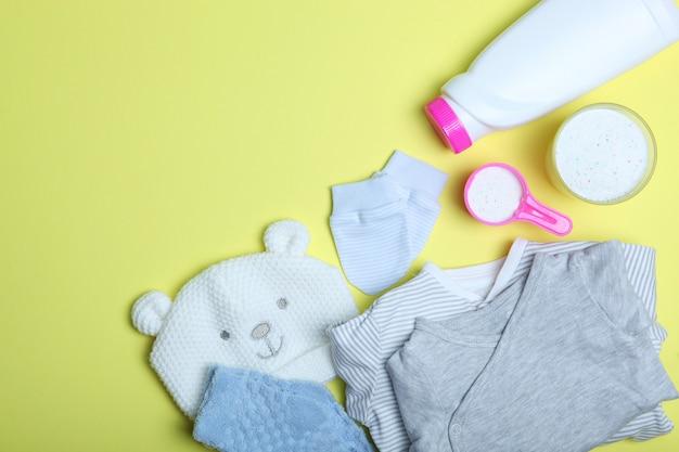Babykleidung und waschmittel auf einer farbigen hintergrundansicht von oben
