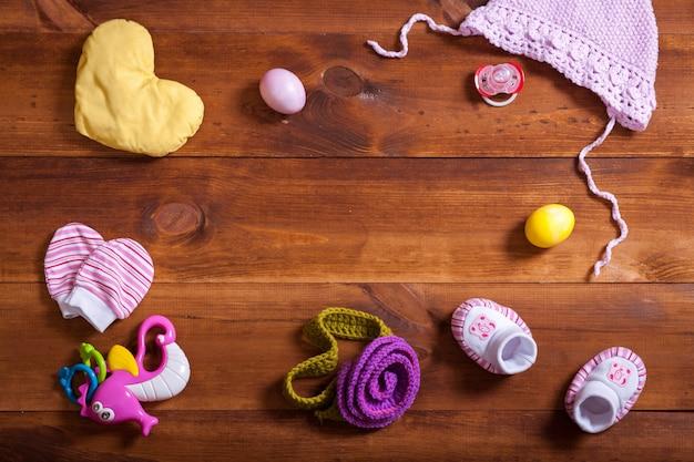 Babykleidungsset, gestrickte baumwollkleidung, kinderspielzeug auf braunem holztisch