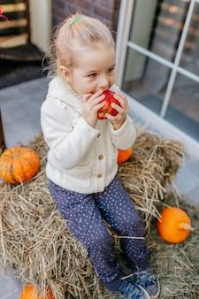 Babykleinkind in der weißen strickjacke, die auf dem heuschober mit kürbisen am portal sitzt und apfel isst.