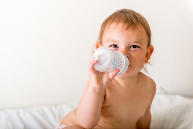 Babykleinkind sitzt auf dem weißen bett, lächelt und trinkt wasser von der plastikflasche