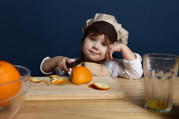 Babykoch in stilvoller schürze und hut, die am tisch mit hölzernem schneidebrett stehen, mit scharfem messer, während frische orangen für salat schneiden. bild des entzückenden kleinen mädchens, das mutter in der küche hilft