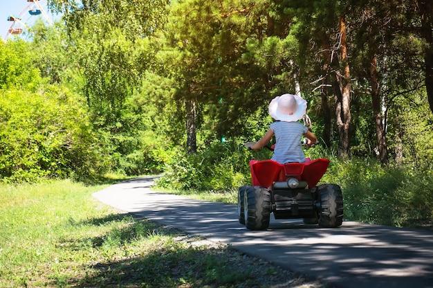 Babymädchen, das auf einem roten atv in einem grünen park unter den strahlen der hellen sonne fährt