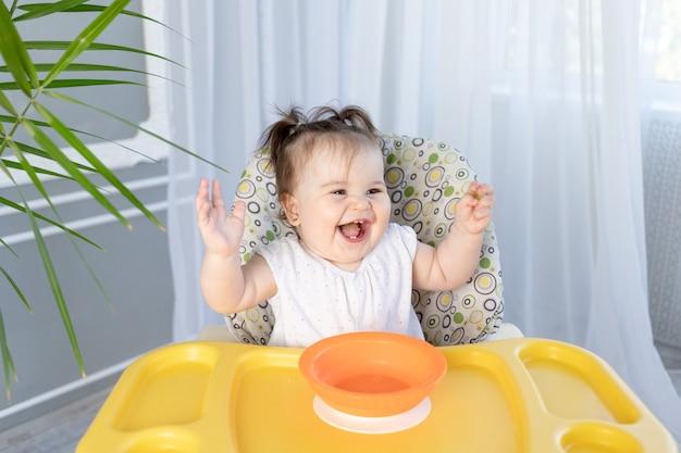 Babymädchen, das in einem hochstuhl sitzt und lacht, babynahrungskonzept