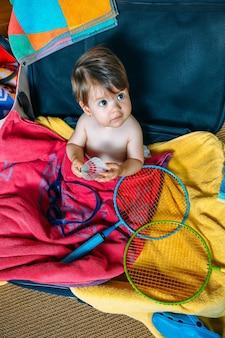 Babymädchen, das in einem koffer sitzt und bereit ist, in den urlaub zu fahren