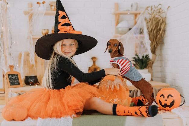 Babymädchen im halloween-hexenkostüm und ein winziger dackel im hundeoverall sitzen auf dem boden