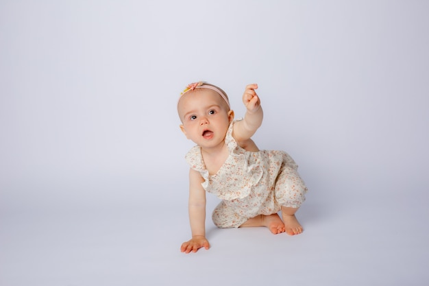 Babymädchen krabbelt auf weißem hintergrund im studio