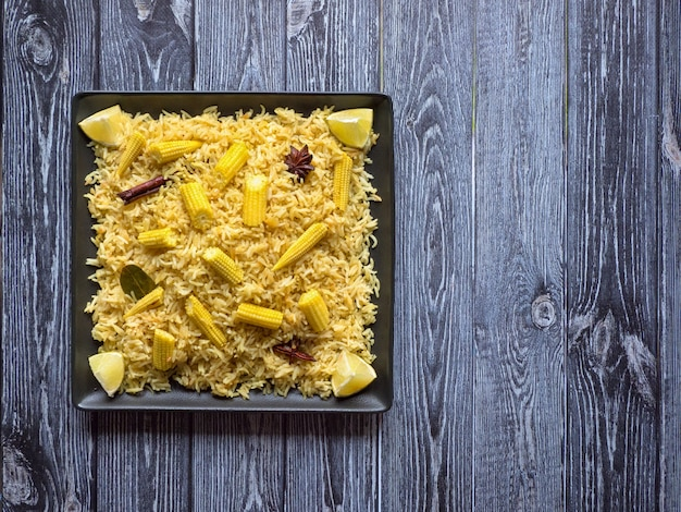 Babymais pulao auf einem holztisch. vegetarisches biryani, indisches essen