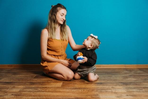Babymode wählen kleid und accessoires mama kleidet das kleine kleinkind babymädchen zu hause mutter