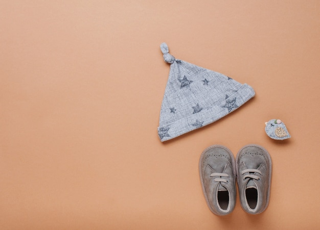 Babymütze und schuhe auf beigem hintergrund mit leerzeichen für text. draufsicht, flach liegen.
