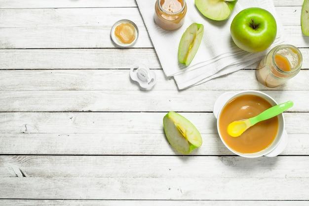 Babynahrung. babypüree aus frischen grünen äpfeln. auf einem weißen hölzernen hintergrund.