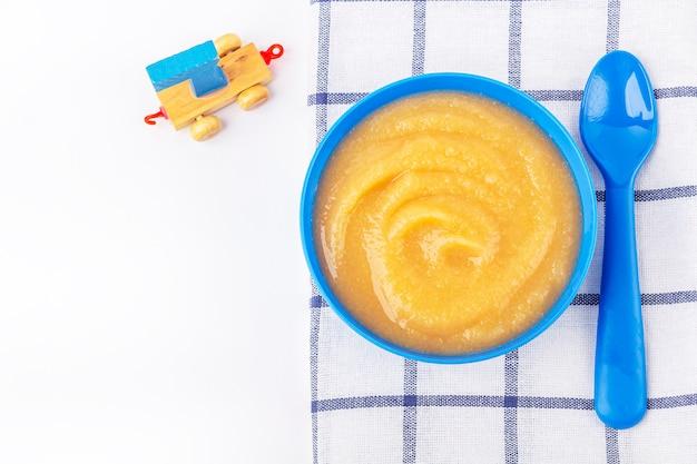 Babynahrung. frisches hausgemachtes apfelmus. blaue schale mit fruchtpüree auf stoff und kinderspielzeug auf tisch. das konzept der richtigen ernährung und gesunden ernährung. bio- und vegetarisches essen