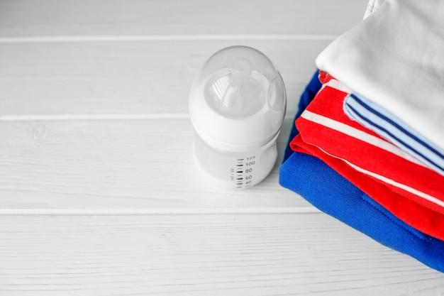 Babynahrung in einer plastikflasche und in einem stapel kleidung