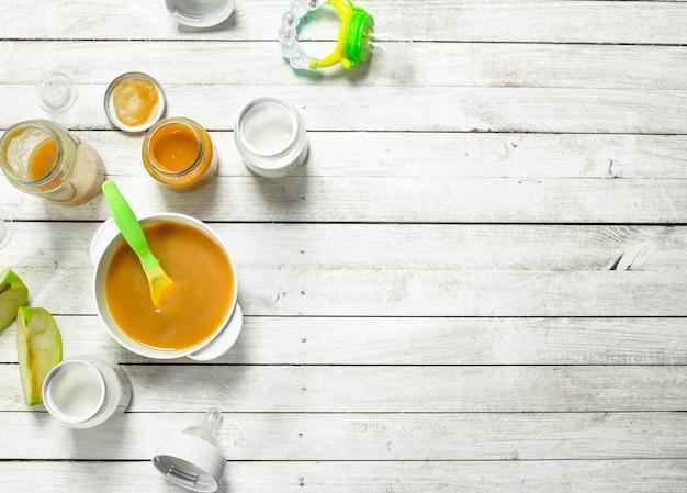 Babynahrung. püree aus grünen äpfeln und frischer babymilch in einer flasche. auf einem weißen hölzernen hintergrund.