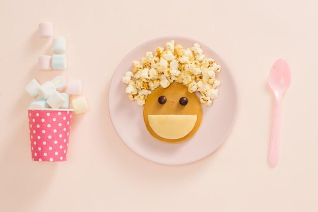 Babypfannkuchen zum frühstück. kreative idee für das kinderdessert: leckere pfannkuchen in form des fröhlichen gesichtes mit dem friseurmachenden popcorn