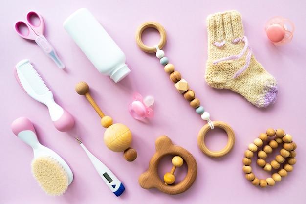 Babypflege-kit auf rosa hintergrund, draufsicht, copyspace. flache komposition mit kinderaccessoires, hintergrund.