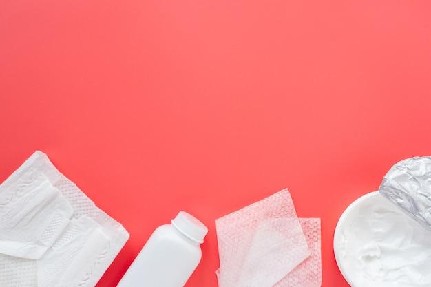 Babypflegekosmetik auf einem rosa hintergrund, flache wohnung, draufsicht, kopienraum für text, modell