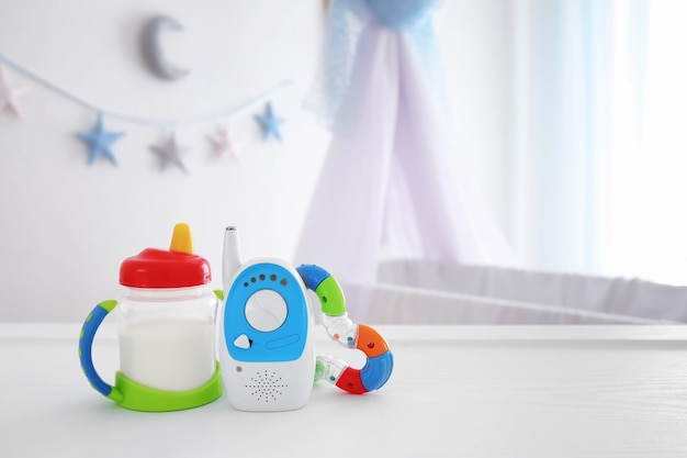 Babyphone, rassel und trinkbecher auf tisch im zimmer. radio kindermädchen