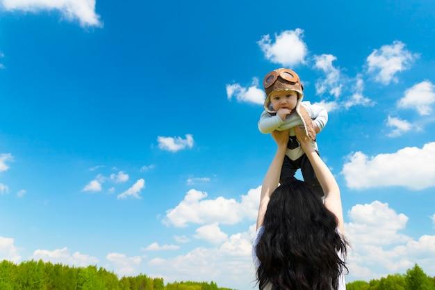 Babypilot, in einem pilotenhut, helm, auf den händen eines jungen, schönen brünetten mädchens. platz kopieren.