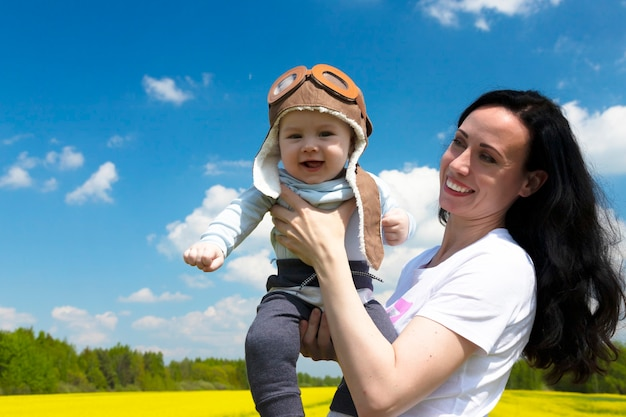Babypilot, in einem pilotenhut, helm, auf den händen eines jungen, schönen brünetten mädchens.