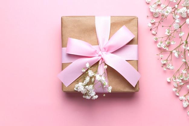 Babys atemblumen und eine geschenkbox mit einem rosa band auf einem rosa hintergrund