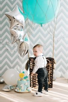 Babys erster geburtstag. nettes lächelndes baby ist 1 jahr alt. das konzept einer kinderparty mit luftballons