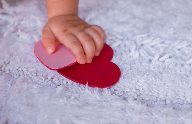 Babys hand hält herzen auf einem weißen hintergrund. ein kind versucht, die herzen von einem weißen, flauschigen teppich zu packen