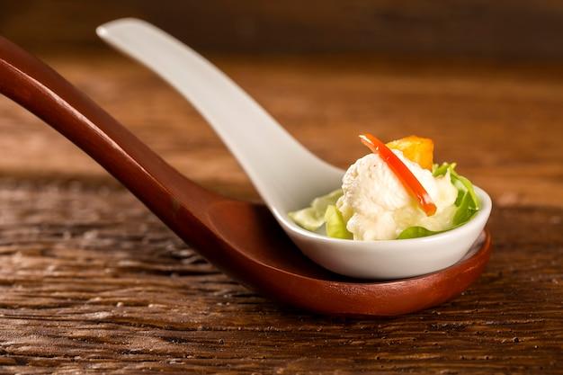 Babysalatsalat, kirschtomaten, palmenherzen, blumenkohlsauce, gebratener maniok und gesalzene schlagsahne in einem löffel. probieren sie gastronomisches fingerfood
